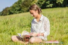 Estudiante joven hermoso que lee un libro en el parque Fotos de archivo libres de regalías