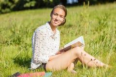 Estudiante joven hermoso que lee un libro en el parque Fotografía de archivo libre de regalías
