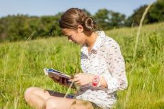 Estudiante joven hermoso que lee un libro en el parque Imágenes de archivo libres de regalías