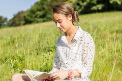 Estudiante joven hermoso que lee un libro en el parque Imagen de archivo libre de regalías