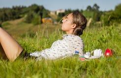 Estudiante joven hermoso que miente en el parque en un día soleado Imágenes de archivo libres de regalías