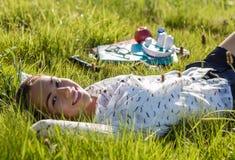 Estudiante joven hermoso que miente en el parque en un día soleado Imagenes de archivo