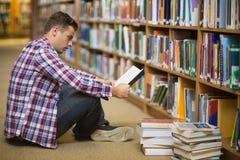 Estudiante joven hermoso que se sienta en el libro de lectura del piso de la biblioteca Fotografía de archivo