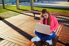 Estudiante joven hermoso que se sienta en un banco en un ordenador en el campus Fotografía de archivo