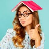 Estudiante joven hermoso que sostiene el libro en su cabeza y que lleva gla Imagen de archivo