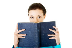 Estudiante joven hermoso que sostiene un libro en su cara. Foto de archivo libre de regalías