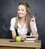 Estudiante joven lindo cerca de la pizarra con la pluma de la calculadora del libro de la copia, espacio de la copia Fotografía de archivo