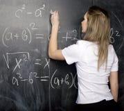 Estudiante joven lindo cerca de la pizarra con la pluma de la calculadora del libro de la copia, espacio de la copia Fotos de archivo