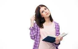 Estudiante joven pensativo que se coloca con el libro Imagen de archivo