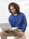 Estudiante joven que aprende en el ordenador portátil en casa Foto de archivo libre de regalías