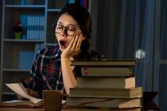 Estudiante joven que bosteza en la noche con los libros Foto de archivo