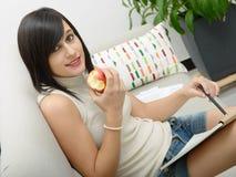 Estudiante joven que come una manzana Imágenes de archivo libres de regalías