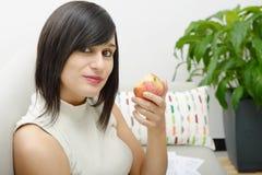 Estudiante joven que come una manzana Fotografía de archivo libre de regalías