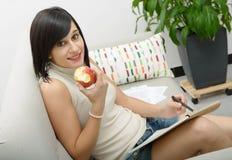 Estudiante joven que come una manzana Imagen de archivo libre de regalías