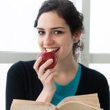 Estudiante joven que come una manzana mientras que lee un libro Imagen de archivo
