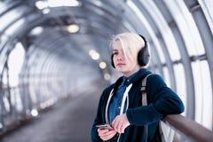 Estudiante joven que escucha la música en auriculares grandes en el subterráneo Imagenes de archivo