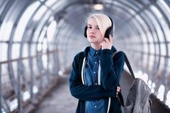 Estudiante joven que escucha la música en auriculares grandes en el subterráneo Fotografía de archivo