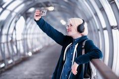 Estudiante joven que escucha la música en auriculares grandes en el subterráneo Fotos de archivo libres de regalías