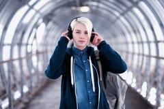 Estudiante joven que escucha la música en auriculares grandes en el subterráneo Foto de archivo
