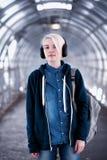 Estudiante joven que escucha la música en auriculares grandes en el subterráneo Fotos de archivo