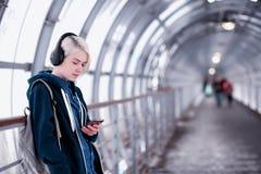Estudiante joven que escucha la música en auriculares grandes en el subterráneo Fotografía de archivo libre de regalías