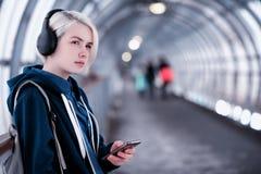 Estudiante joven que escucha la música en auriculares grandes en el subterráneo Imagen de archivo libre de regalías