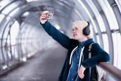 Estudiante joven que escucha la música en auriculares grandes en el subterráneo Imagen de archivo