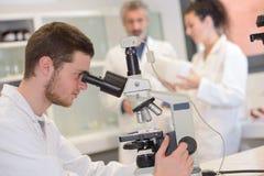 Estudiante joven que hace el reserch con el microscopio Imagen de archivo