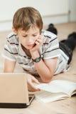 Estudiante joven que hace su schoolwork en casa Imagenes de archivo