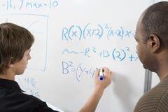 Estudiante joven que hace sumas de la matemáticas Imagen de archivo