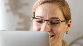 Estudiante joven que hace una comunicación video en la tableta de la PC con los amigos 4K almacen de metraje de vídeo