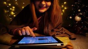 Estudiante joven que lee el feliz poema de los hristmas en la tableta Foto de archivo