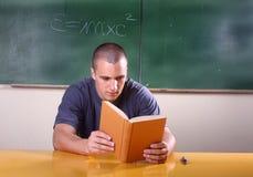 Estudiante joven que lee un libro Imágenes de archivo libres de regalías