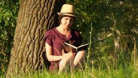 Estudiante joven que lee un libro en el parque Cultura, lectura, educación Muchacha que se sienta por el árbol Movimiento de la c almacen de metraje de vídeo