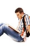 Estudiante joven que lee un libro en el suelo Fotos de archivo libres de regalías
