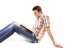 Estudiante joven que lee un libro en el suelo Fotos de archivo