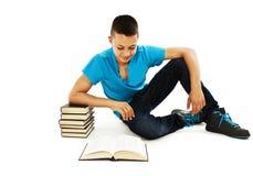 Estudiante joven que lee un libro en el suelo Imagenes de archivo