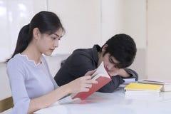 Estudiante joven que lee un libro solamente mientras que su compañero de clase es slee fotografía de archivo