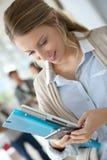 Estudiante joven que manda un SMS con smartphone Fotos de archivo