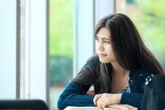Estudiante joven que mira hacia fuera la ventana mientras que estudia Foto de archivo libre de regalías