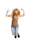 Estudiante joven que salta con los pulgares para arriba Fotografía de archivo