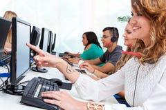 Estudiante joven que señala con el finger en la pantalla de ordenador. imagenes de archivo
