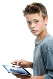 Estudiante joven que se coloca con la tableta. Fotos de archivo