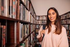 Estudiante joven que se coloca en la biblioteca Fotos de archivo libres de regalías