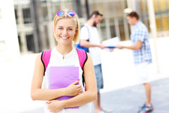Estudiante joven que se coloca y que sonríe en el campus foto de archivo