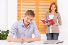 Estudiante joven que se prepara a los exámenes y a la sonrisa Imagenes de archivo