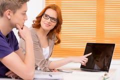 Estudiante joven que se prepara a los exámenes y que mira la pantalla Imagen de archivo libre de regalías