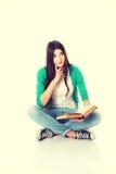 Estudiante joven que se sienta con el libro, leyendo Imagen de archivo
