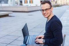 Estudiante joven que se sienta en un banco con el ordenador portátil. Imágenes de archivo libres de regalías