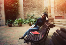 Estudiante joven que se sienta en un banco en una calle pintoresca Imagenes de archivo